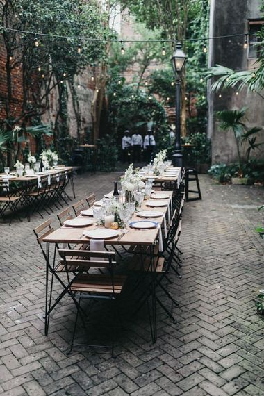 Outdoor Wedding Reception in a Courtyard with Plants and Festoon Light Wedding Decor