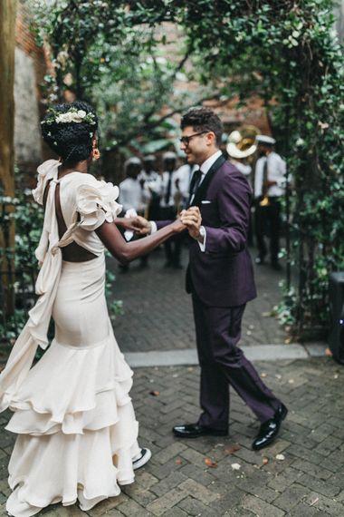 Stylish Bride in Ruffled Johanna Ortiz Wedding Dress and Groom in Burgundy Tuxedo Dancing