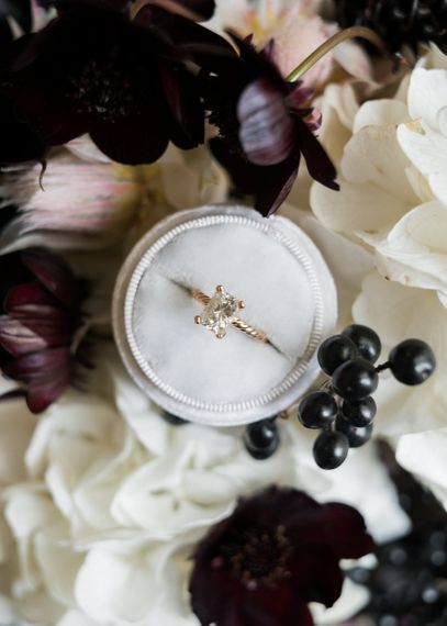 Diamond Engagement Ring in Ring Box Surrounded by Wedding Flowers