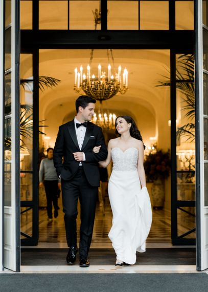 Glamorous Bride and Groom Arm in Arm Walking Out of Their Wedding Venue