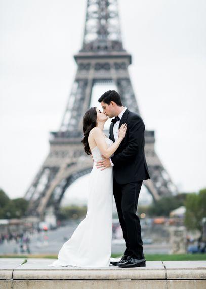 Bride in Tara Keely Wedding Dress and Groom in Black Tie Suit  Embracing in Front of the Eiffel Tower