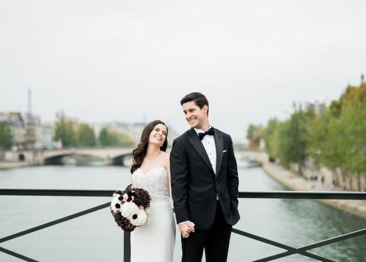 Bride in Tara Keely Wedding Dress and Groom in Black Tie Suit Posing in Front of the River Seine