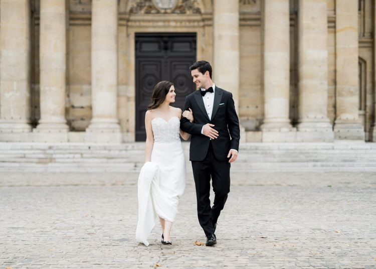 Bride in Off the Shoulder Tara Keely Wedding Dress and Groom in Black Tuxedo Hand in Hand Through the Streets of Paris