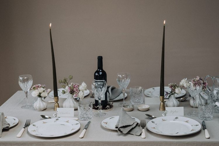 Intimate tablescape with neutral linens, black taper candles and blush flowers in bud vases