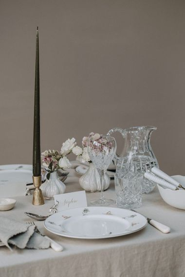 Place setting with patterned plate, taper candle and crystal glassware