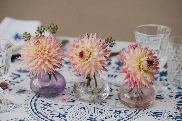coloured bud vases with flower stems