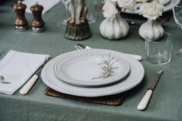 Place setting with leather mat, printed tableware and ivory cutlery