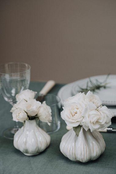 Ceramic bud vases filled with white flower stems
