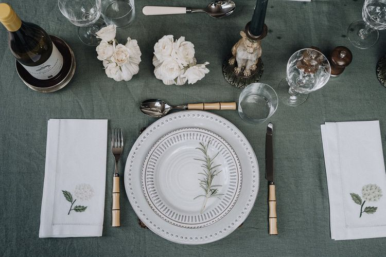Place setting with patterned tableware, bamboo style cutlery and embroidered table napkins