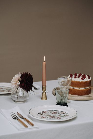 Place setting with patterned tableware, candles sticks and bud vases