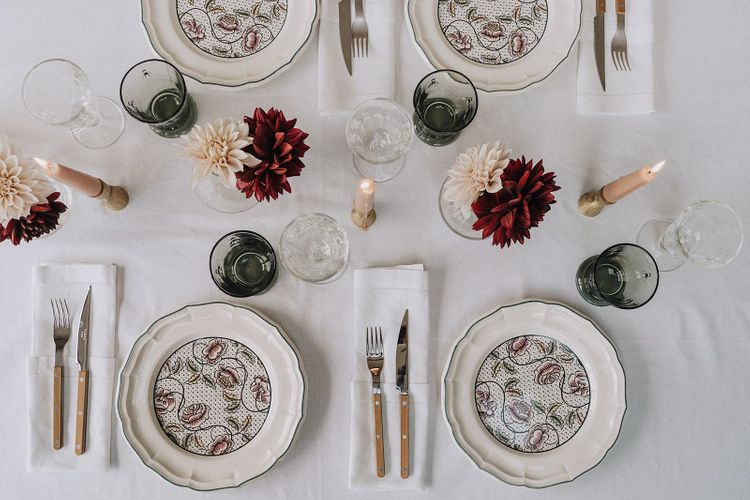 Intimate table setting with patterned tableware, candlesticks and bud vases.