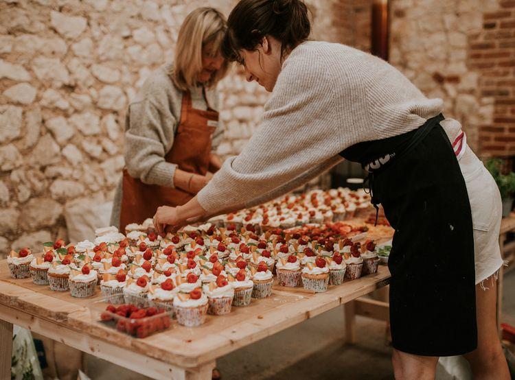 Groom's sister decorates handmade cupcakes