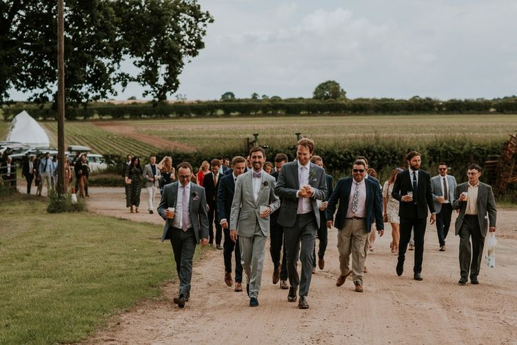 Groom and guests make their way to wedding ceremony