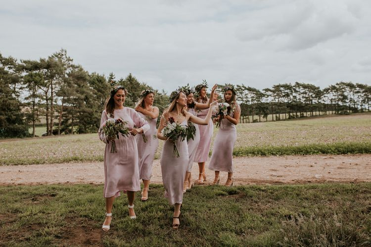 Bridal party on their way to outdoor ceremony at Norfolk wedding venue