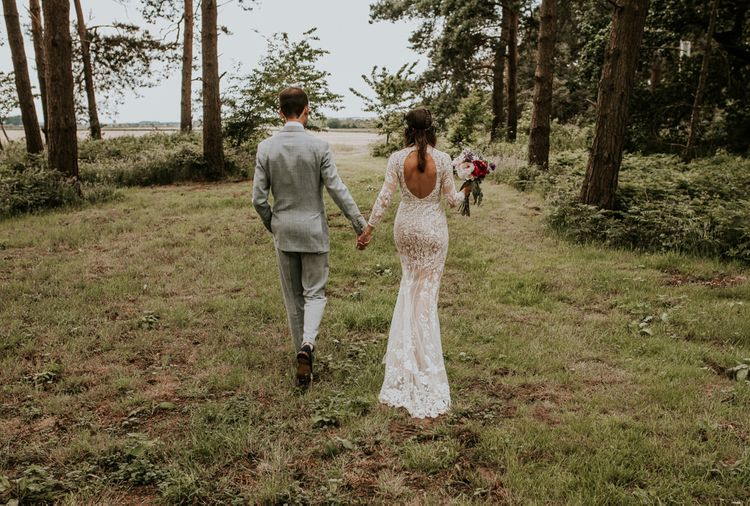 Open back lace bride dress with groom in grey suit