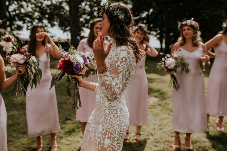 Bride in flower crown and bridesmaids in pink dresses