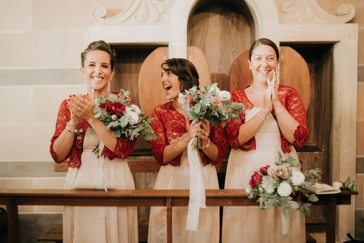 Bridesmaids in red lace cover-ups applaud bride and groom