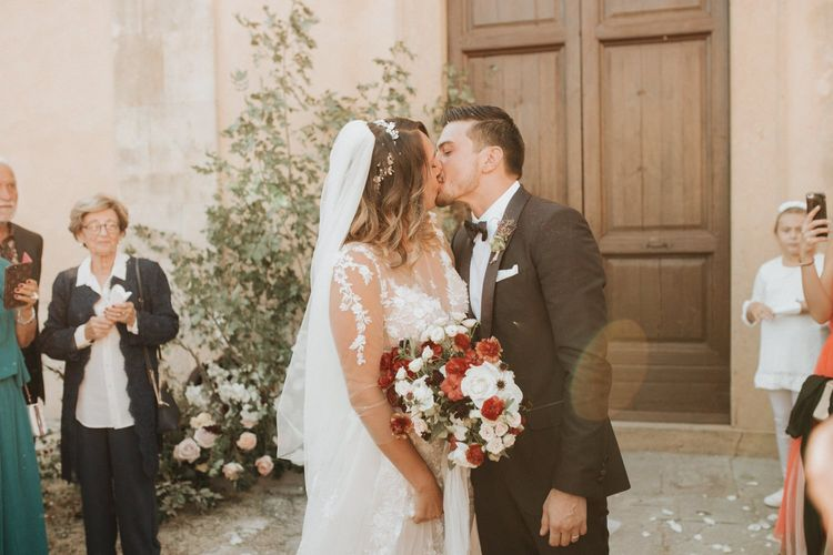 Bride and groom kiss after ceremony with blush and red bouquet