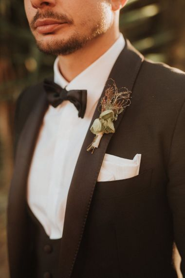 Groom in black tuxedo with bowtie and buttonhole