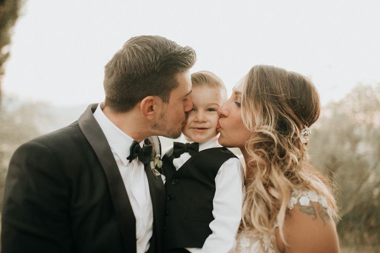 Bride and groom kiss their son at destination wedding