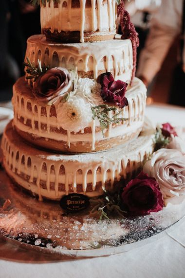 Candle lit drip wedding cake with flower decor
