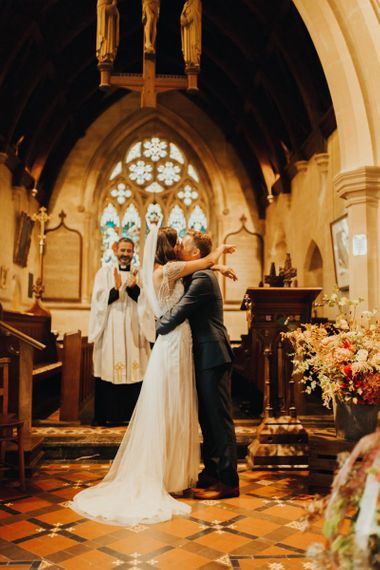 Bride in Maggie Sottero wedding dress and groom kiss at altar