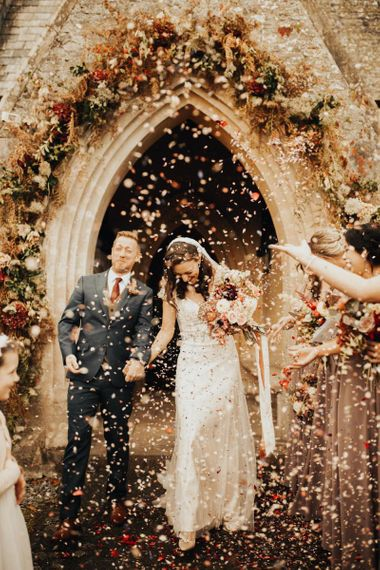 Confetti exit for groom and his bride in Maggie Sottero wedding dress