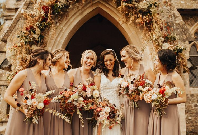Bride in Maggie Sottero wedding dress with bridesmaids in neutral dresses