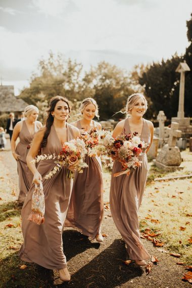 Bridesmaids in neutral dresses making their way to the church ceremony