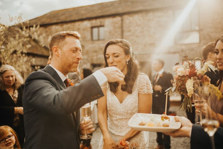 Bride in Maggie Sottero wedding dress with groom eating canapés