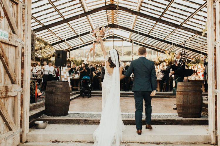 Groom enters reception with bride in Maggie Sottero wedding dress