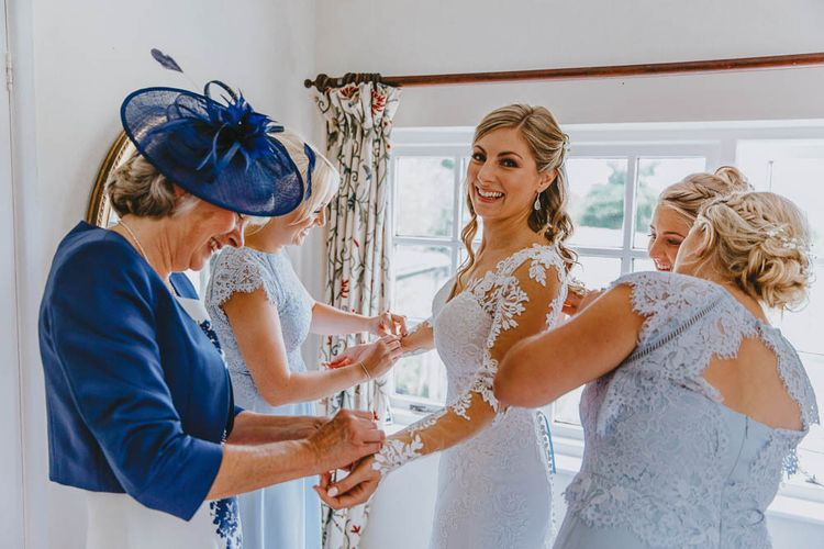 Mother of The Bride and Bridesmaids in Blue Dresses Helping the Bride into Her Lace Wedding Dress on the Wedding Morning