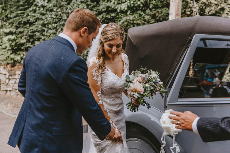 Groom in Blue Ted Baker Suit Helping His Bride in Lace Wedding Dress into the Vintage Wedding Car