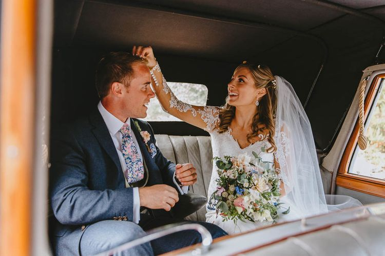 Bride in Lace Sincerity Bridal Wedding Dress Picking Confetti Out of Her Grooms Hair in the Back of The Vintage Wedding Car