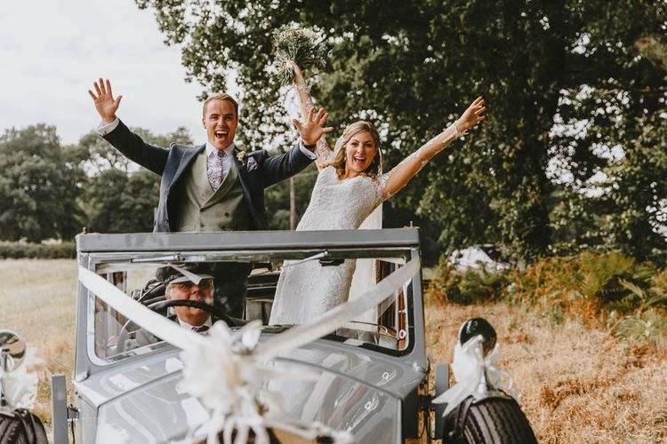 Bride in Lace Sincerity Bridal Wedding Dress And Groom in Blue Ted Baker Suit Standing Up in Their Vintage Wedding Car