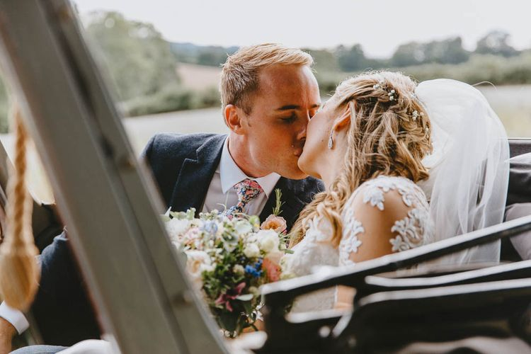 Bride and Groom Kissing in the Back of their Vintage Wedding Car
