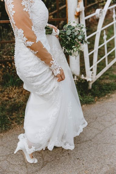 Bride in Lace Sincerity Bridal Wedding Dress with Long Sleeve Holding Up her Train