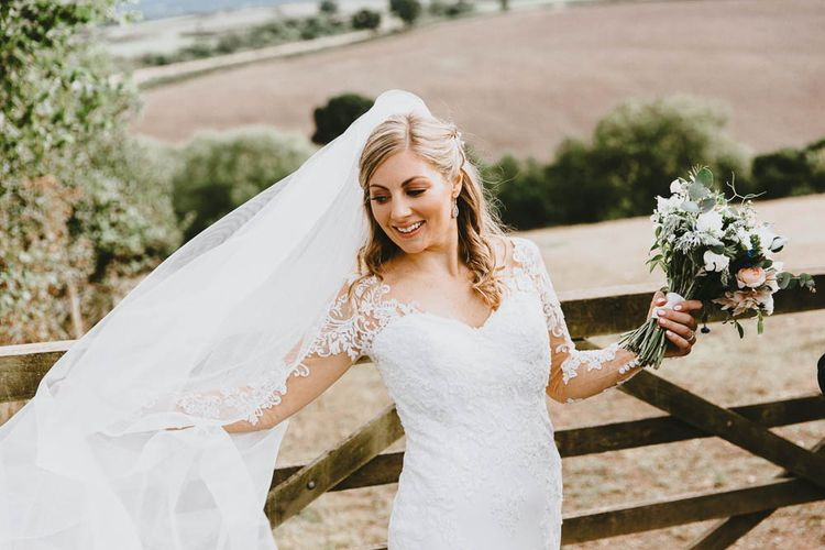 Bride in Lace Sincerity Bridal Wedding Dress with Long Sleeves and Wedding Veil