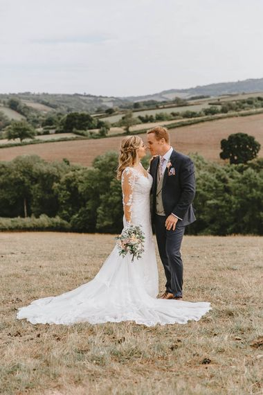 Bride in Lace Sincerity Bridal Wedding Dress and Groom in Blue Ted Baker Suit Embracing in Field