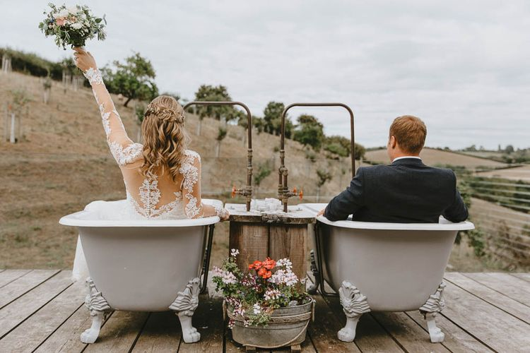 Bride in Lace Sincerity Bridal Wedding Dress and Groom in Blue Ted Baker Suit Sitting in Twin Rolltop Baths on The Old Piggyery Veranda at Devon Wedding Venue Windout Barn
