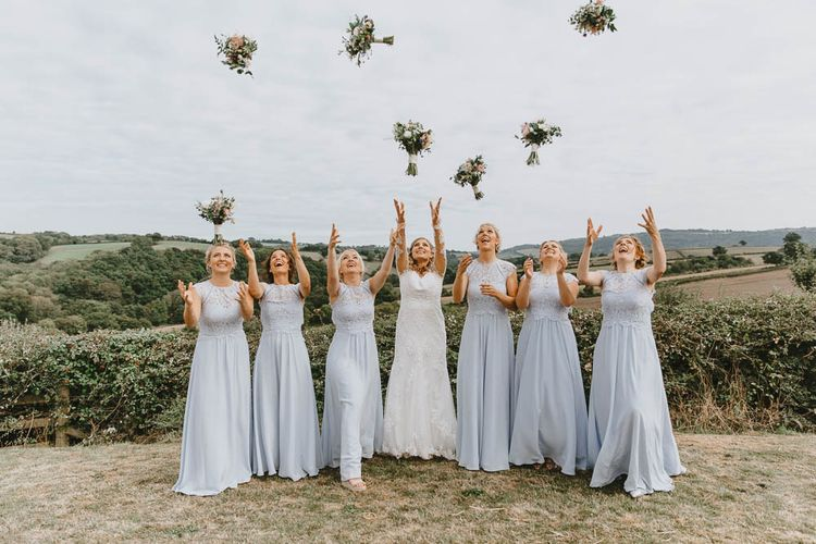 Bridal Party Portrait with Bridesmaids in Blue Lace Dresses and Bride in Longsleeve Sincerity Bridal Wedding Dress Throwing Their Bouquets in the Air