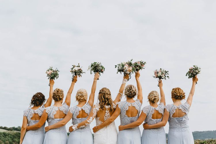 Bridal Party Portrait with Bridesmaids in Blue Lace Dresses and Bride in Longsleeve Sincerity Bridal Wedding Dress Holding Their Bouquets in the Air