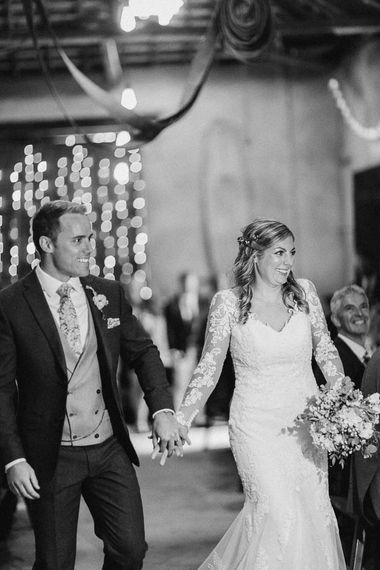 Bride in Lace Sincerity Bridal Wedding Dress and Groom in Blue Ted Baker Suit Entering Wedding Reception Holding Hands