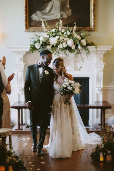 Bride and groom walk up the aisle at Kirtlington Park wedding