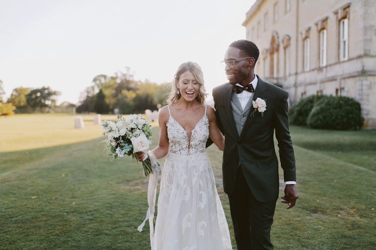 Groom in tuxedo with grey waistcoat and bride in lace wedding dress
