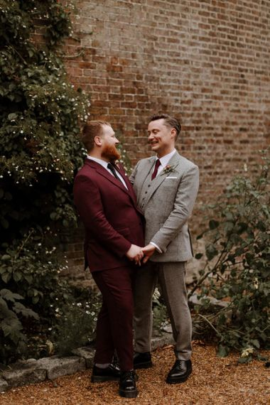 Portrait of groom in burgundy and beige checked suits at their Syon Park wedding