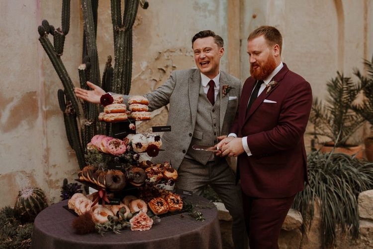 Groom and groom cutting the doughnut tower wedding cake