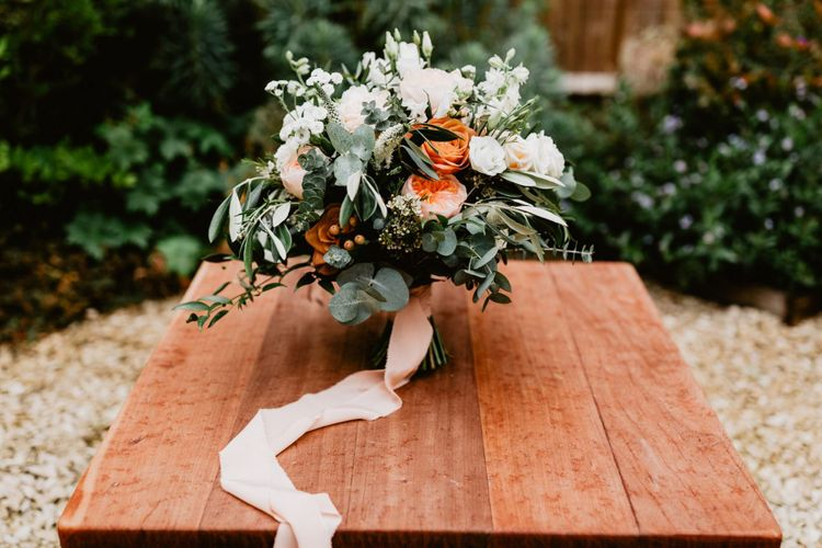 White and peach wedding bouquet tied with ribbon for 2020 wedding