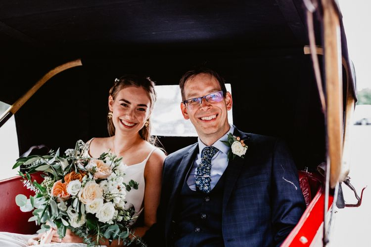 Bride and groom arrival in vintage wedding car