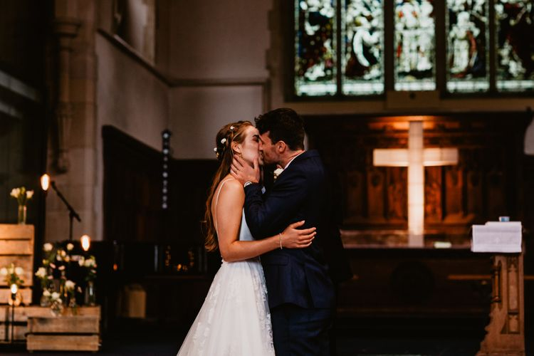 Bride and groom kiss during church wedding ceremony
